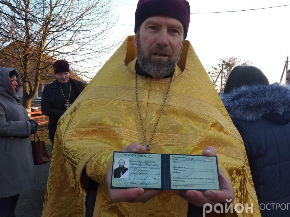 Отець Олександр демонструє своє посвідчення священика