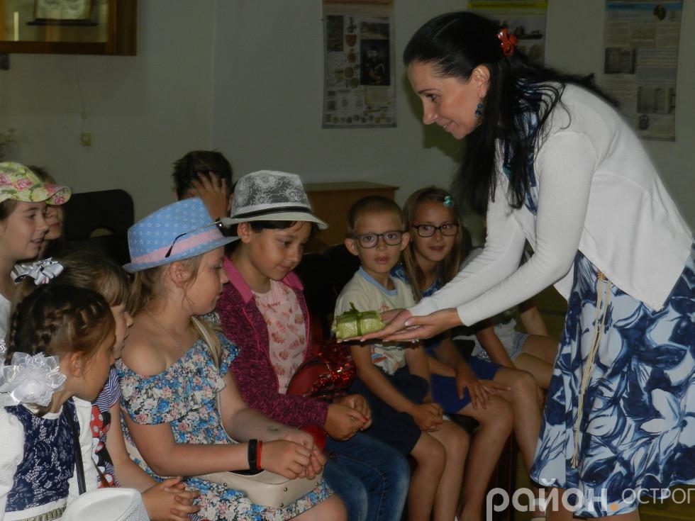 Олена Медвєдєва демонструє дітлахам мінікнигу