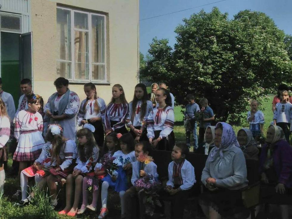 Молодші школярі та місцеві жителі уважно слухають про події Другої світової війни