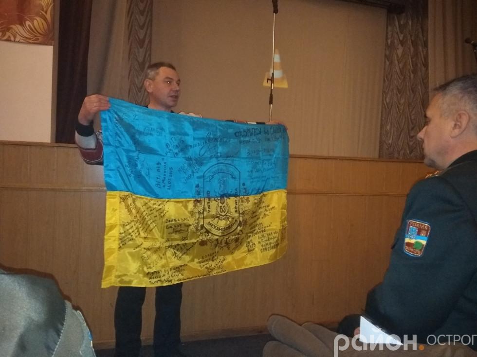 Віктор Романчук демонструє прапор із підписами бойових побратимів. Каже, дуже ним дорожить