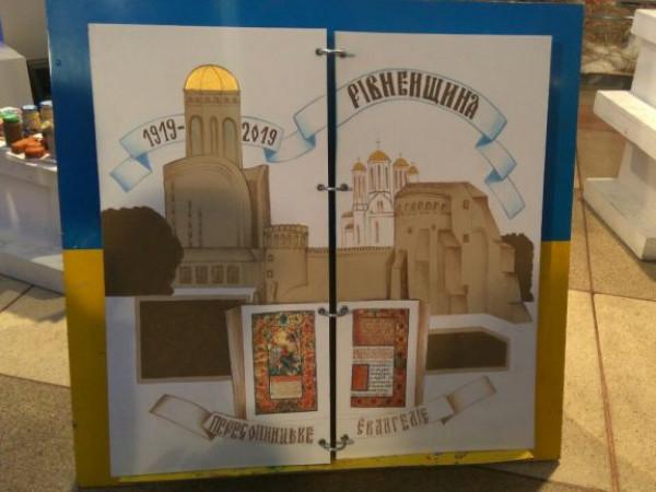 Розворот мандрівної книги, на якому зображена Рівненщина, зокрема замок Острозьких